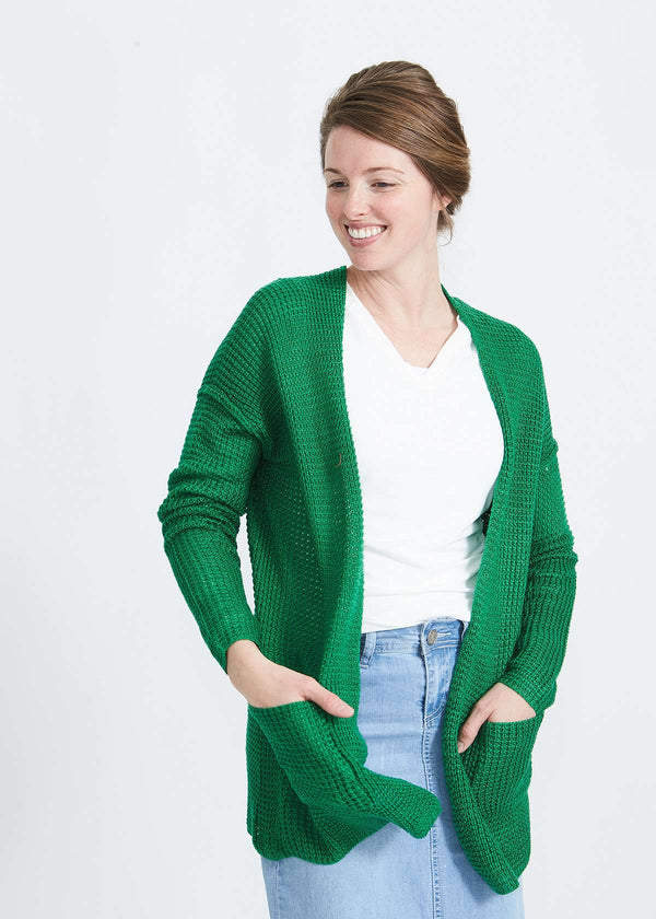Woman wearing a green or coral waffle knit cardigan