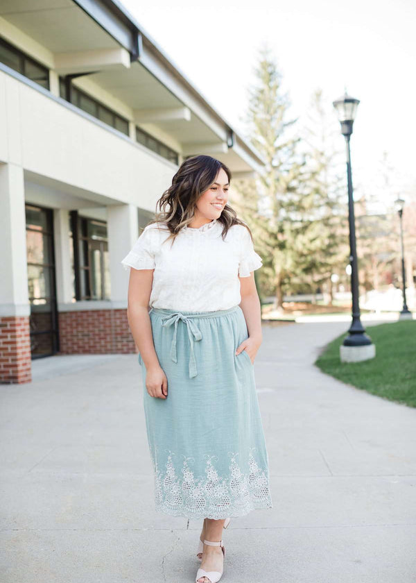 Woman wearing a mint green cotton midi skirt with a self tie and feminine crochet lace detail at the bottom hem