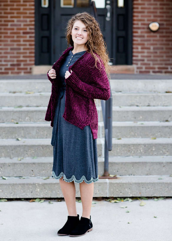 Woman wearing a wine colored shrug chenille sweater with open front and extra length in the back.