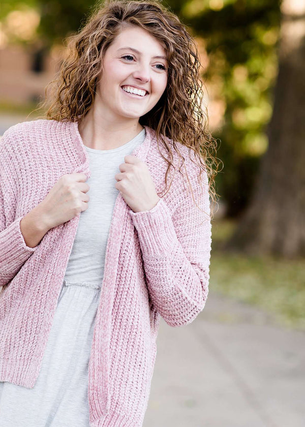 Woman wearing a pink shrug chenille sweater with open front and extra length in the back.