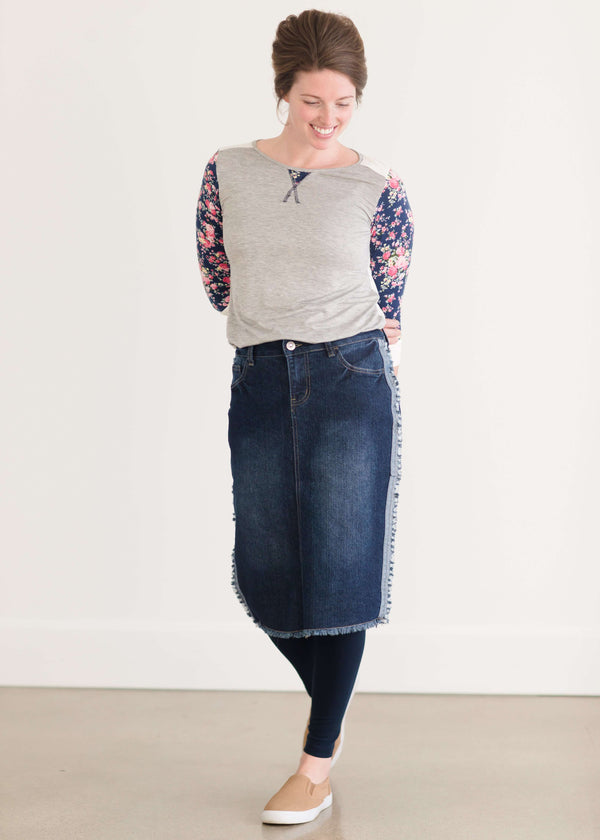Woman wearing a below the knee jean skirt that has fringe and fray detail on the hem and side seams.