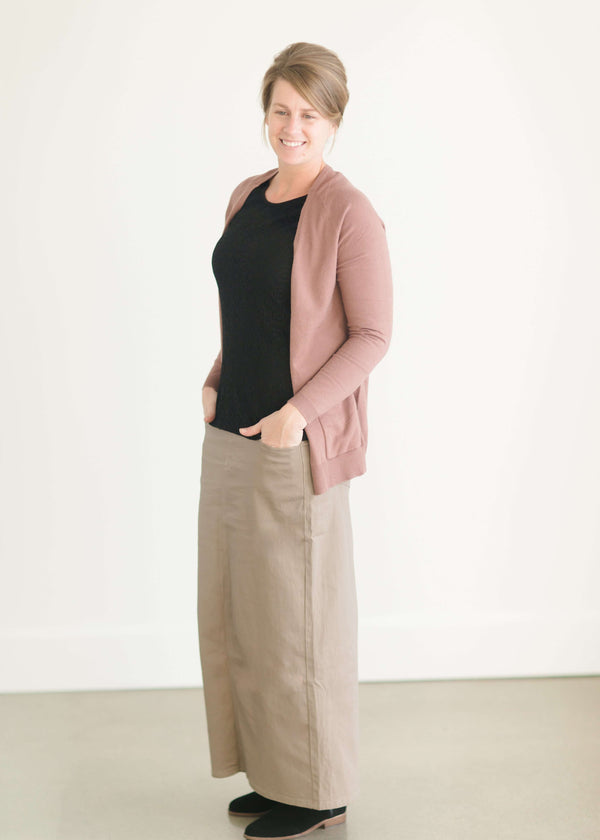 Woman wearing a long khaki twill skirt with a black lace top and a modest cardigan.