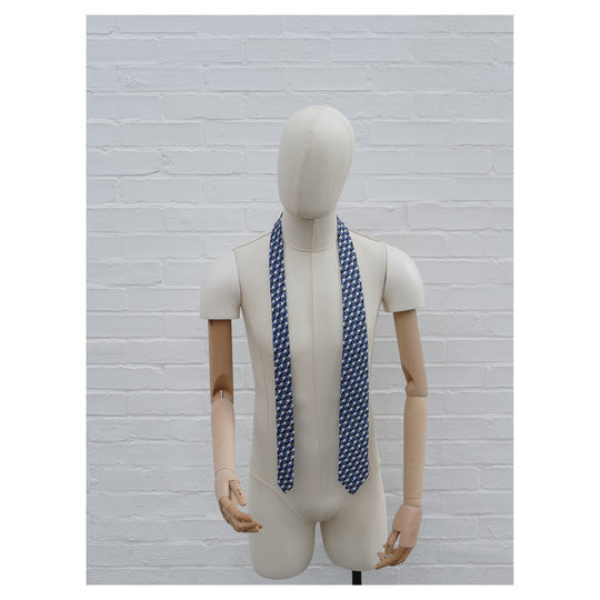 Eclipse silk tie on a mannequin. Blue & grey graphical print.
