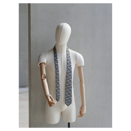 Freedom Tie silk tie designed by Niki Fulton. A graphical bronze and blue print. Seen here on a mannequin.