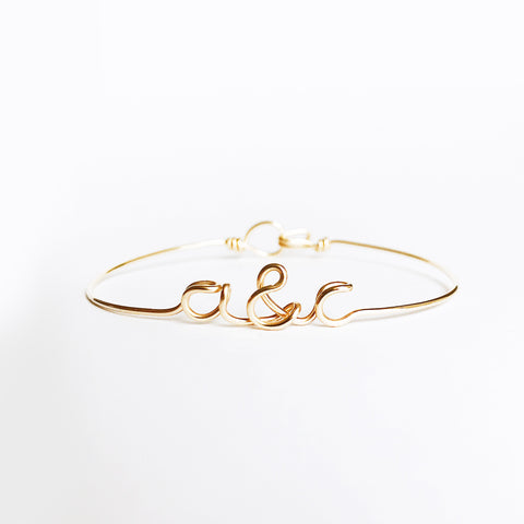 Personalised Initials with ampersand a&c wire bangle bracelet in Yellow Gold handmade by Rachel and Joseph Jewellery UK