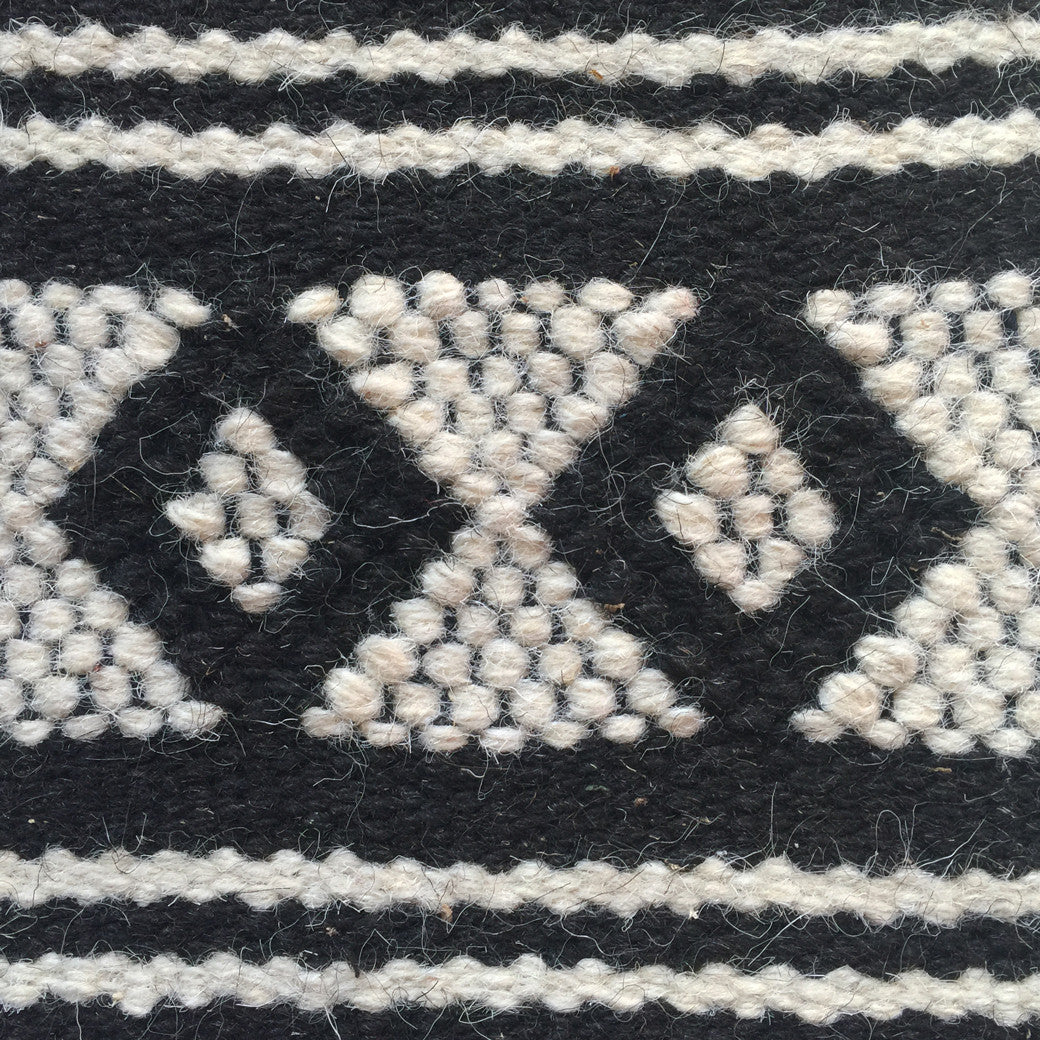 SUNDAY / MONDAY Handwoven 100% Wool Indian Flatweave Rug, Mandvi, Black and white wool area rug made in tribal indigenous traditional motifs triangle zig-zag diamond.  Handmade in Kutch, Gujarat detail