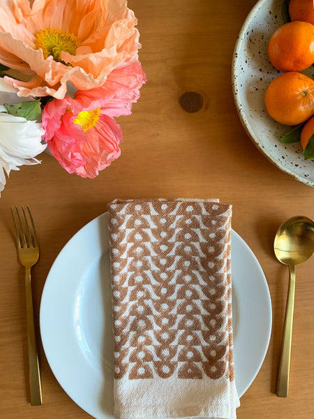 '70s inspired hand block printed neutral napkins by SUNDAY/MONDAY in a warm brown, featuring a geometric pattern.