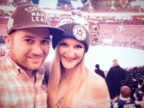 Andrew and Megan Kelly at a Toronto Maple Leafs game wearing Maple Leaf fan hats.