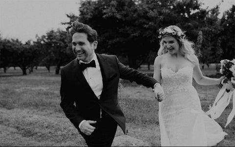 Andrew and Megan holding hands running together on their wedding day.