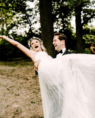 Andrew Kelly lifts up Megan Kelly on their wedding day. Megan's hand in the air, smile wide across her face.