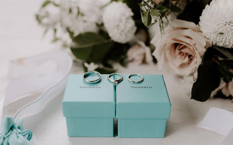 Megan and Andrews engagement ring and wedding bands on top of Tiffany's boxes.