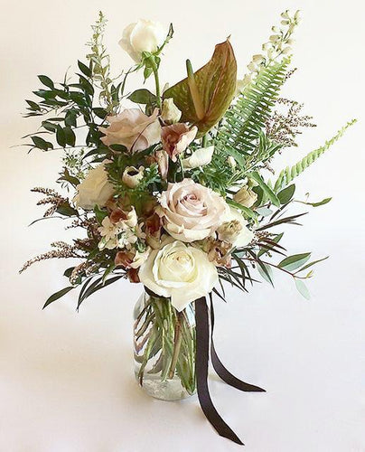 A flower jar bouquet full of seasonal flowers in a white and pastel pink color palette with bursts of greenery and lots of texture.