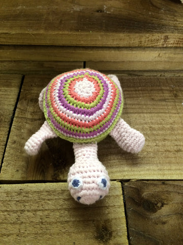pink turtle soft toy with a multi coloured shell, displayed on a wooden background.