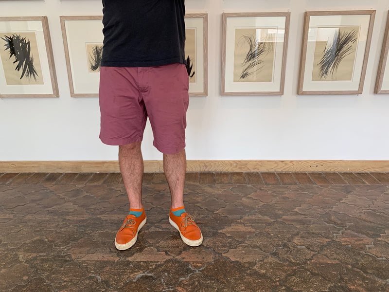 KARL Persimmon men's orange leather sneakers by Tracey Neuls in front of art exhibition in south of France