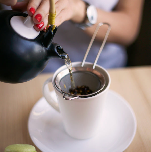 hands holding a black teapot pouring tea to the cup through a metal steeper