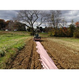 A farmer on a tractor in a filed laying out a long roll of organic natural paper mulch over the soil and land