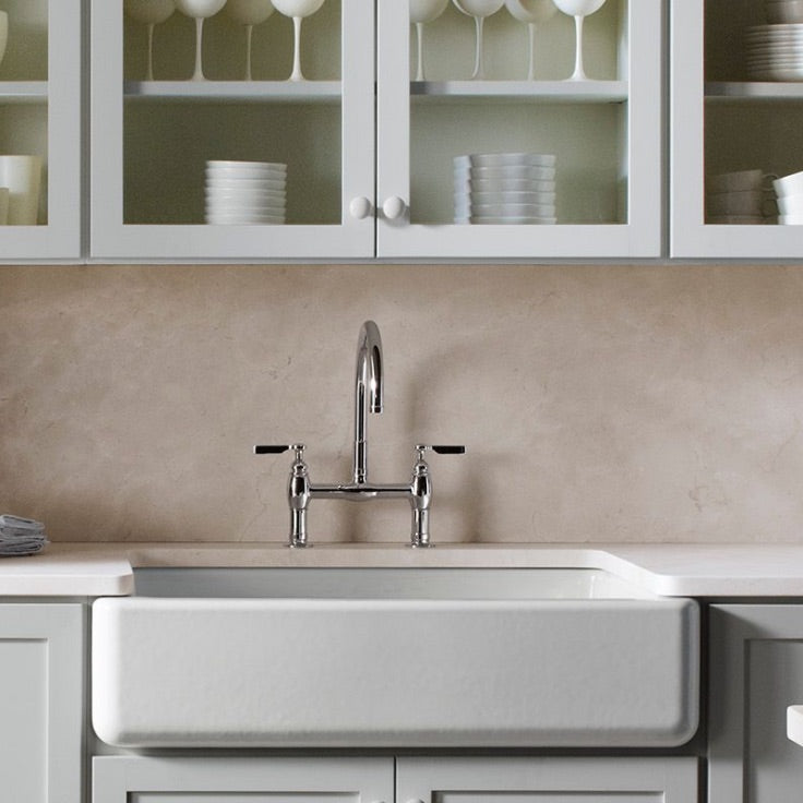 Cast iron farmhouse sink in modern kitchen with tope countertop
