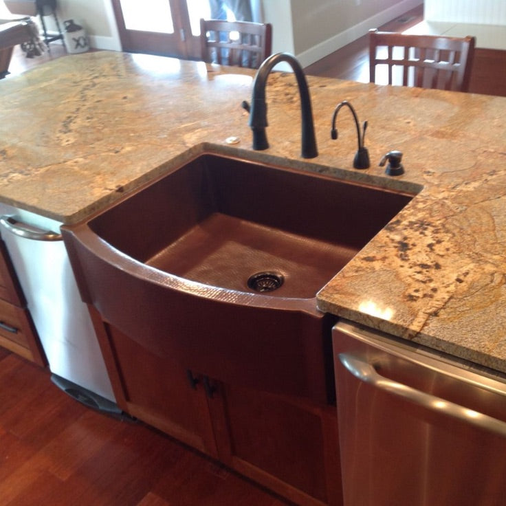 Copper farmhouse sink installed in rustic kitchen