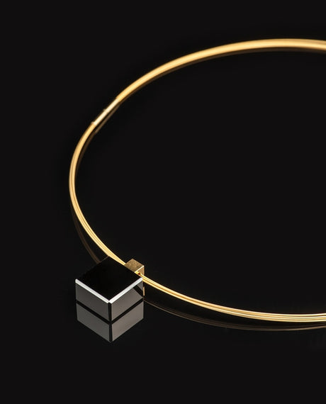 Black glass cube on gold necklace