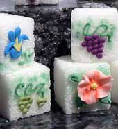 Decorated sugar cubes with purple and green grapes, orange and blue flowers