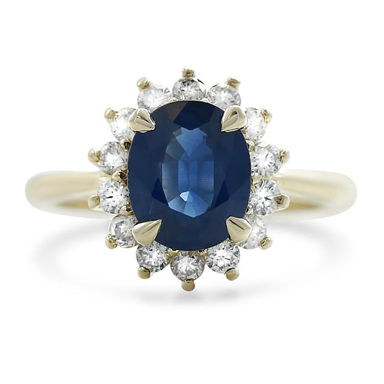 oval blue sapphire ring with a flower round white diamond halo 14k yellow gold prong set