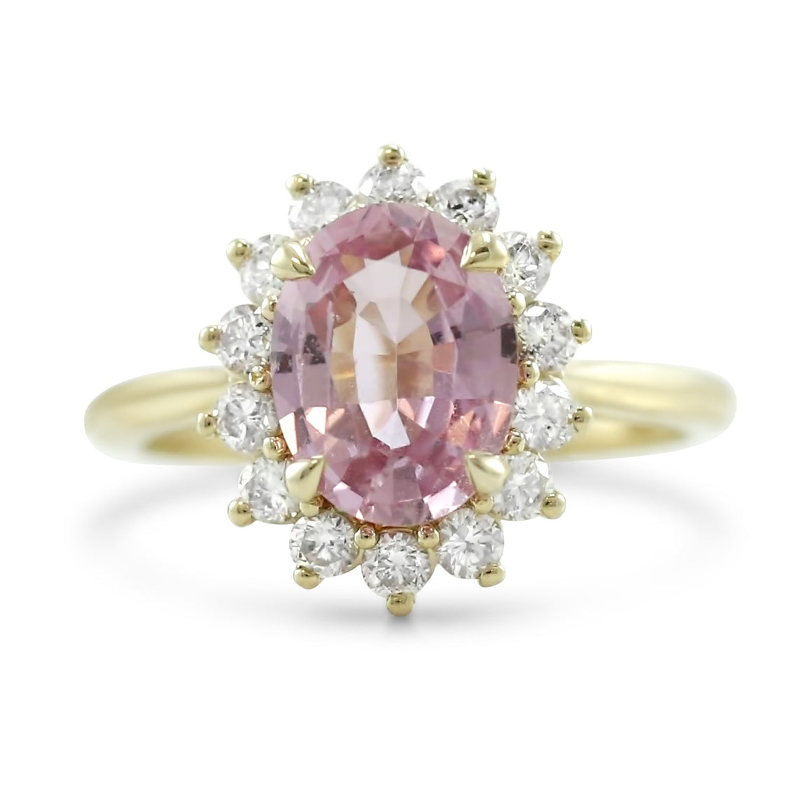 oval pink sapphire prong set engagement ring with a diamond halo 14k yellow gold
