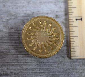 closeup of sun brass stamp head