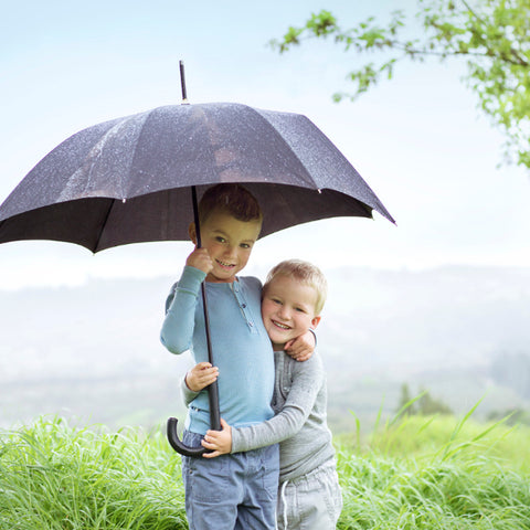 two kids with an umbrella
