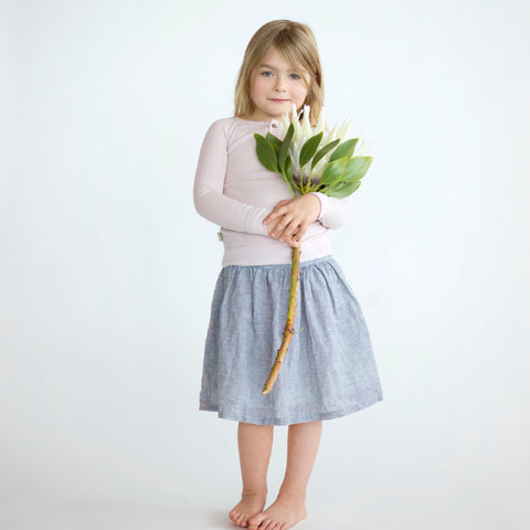 young girl wearing merino top and skirt holding a flower