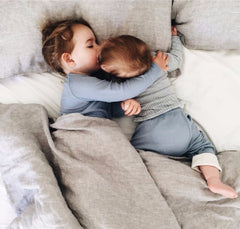 baby girl and baby boy snuggling in bed