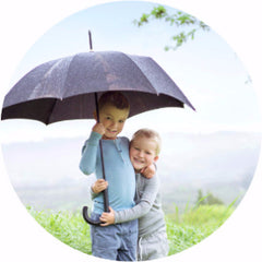kids outside under an umbrella
