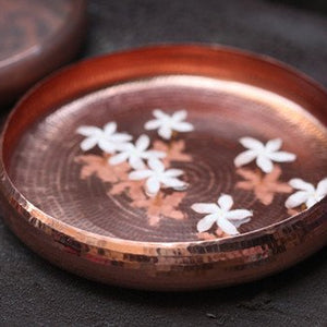 Copper dish styled with water and floating flowers in it