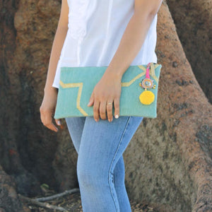 Model with Mint colored bohemian dhurrie clutch