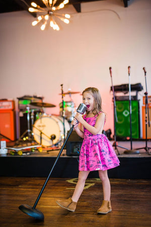 Girl singing into microphone in a pink Toddler pinafore dress with dinosaurs printed all over. Matching sister outfits newborn and toddler available