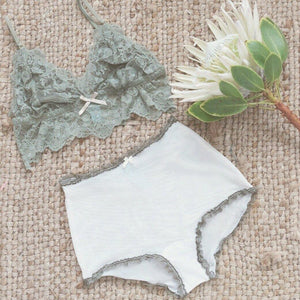 Takkleberry vintage inspired high-waisted knickers in white and olive green. Waist fitting panty briefs, with cream white soft mesh and olive green frill lace trim. Photo flatlay, beautiful lingerie high-rise underwear, white snow king protea and lace bralette in olive green