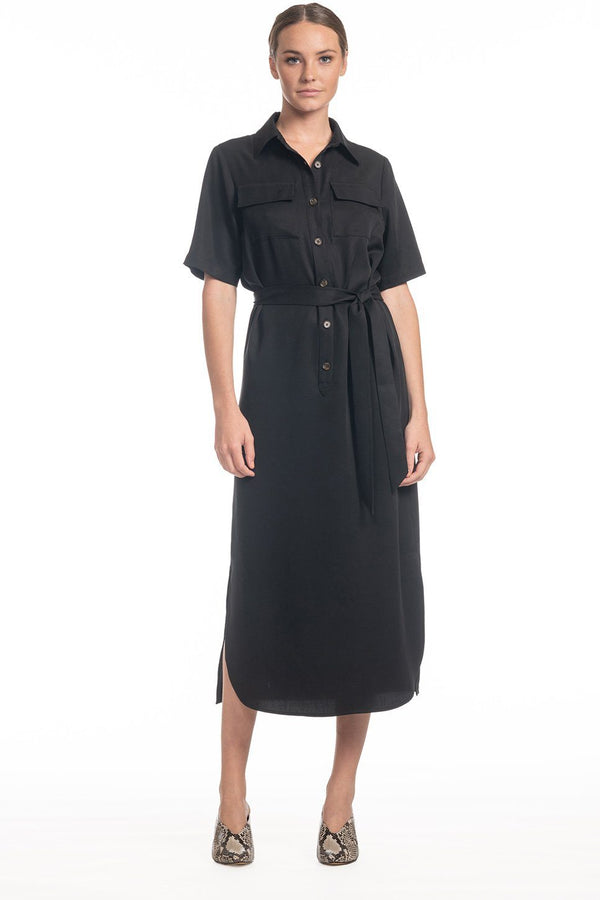 One model wearing a ladies utility tie waist shirt dress in black on a white background.