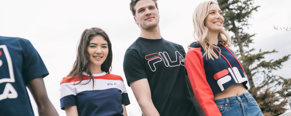 Shop Fila; group of friends wearing Fila Clothing and Levi's Denim while walking through a park