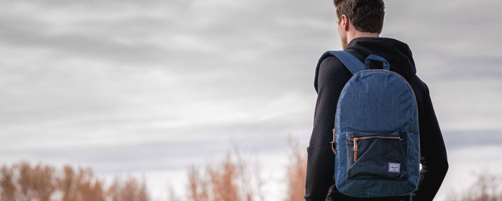 Shop Herschel; man wearing Blue Denim Settlement Backpack standing against dramatic sky