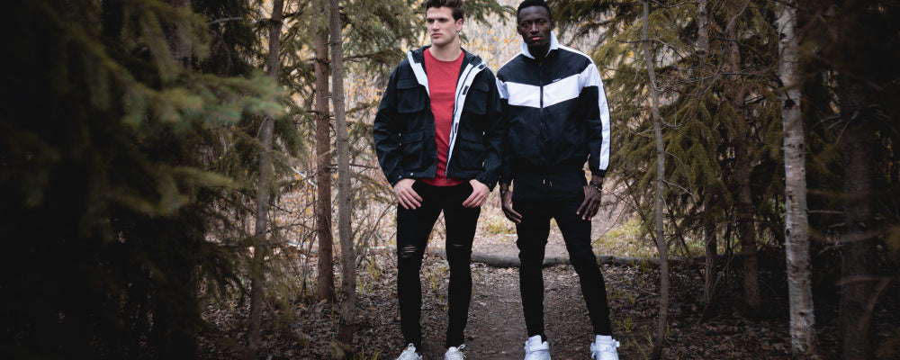 Shop Kuwallatee; two men wearing Kuwallatee jackets, jeans, and tees standing in wooded area