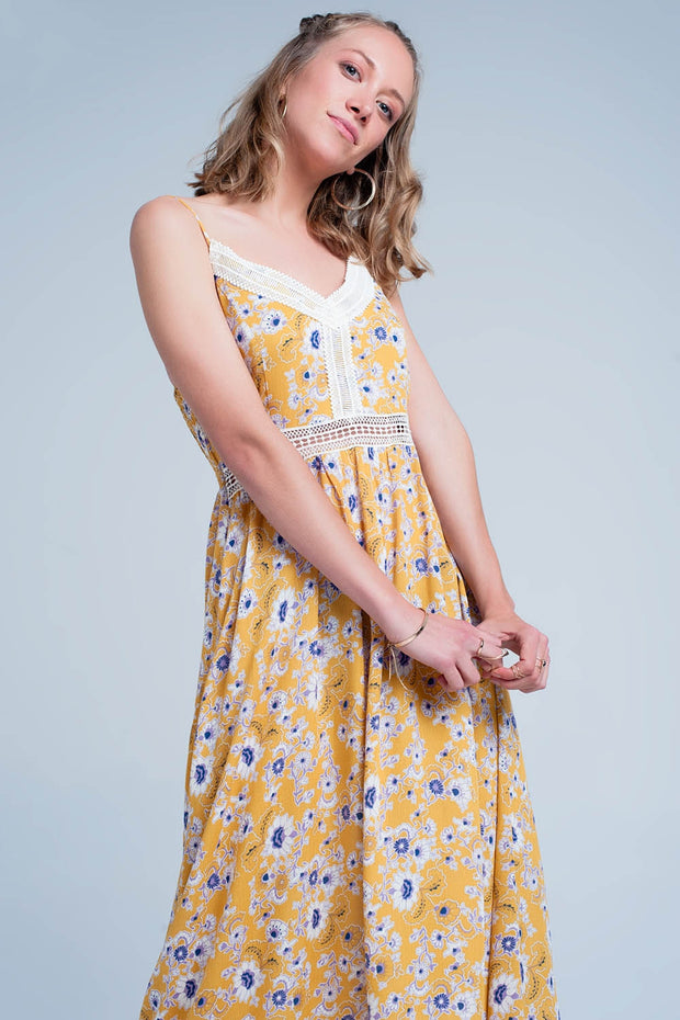 Yellow dress with flower print made from soft viscose. This dress has spaghetti straps and a v neck. The v neck is lined with lace and there are crochet cutouts by the stomach.