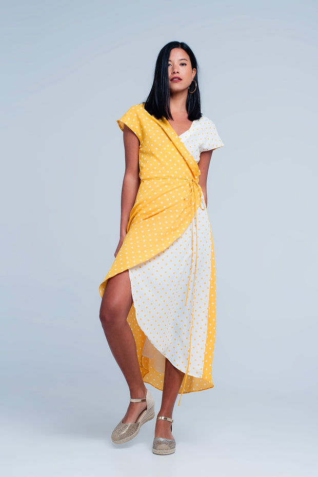 Long yellow and white dress with polka dots in white and yellow. This dress has short sleeves, a V-neck and a thin strap at the waist to close the dress.