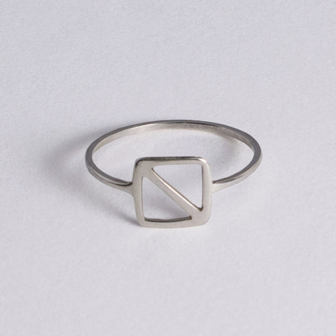 "Silver ring inspired by the nautical flag for the letter ""O"" the maritime signal for ""man overboard!"" The minimal design is a square with a diagonal line from corner to corner."