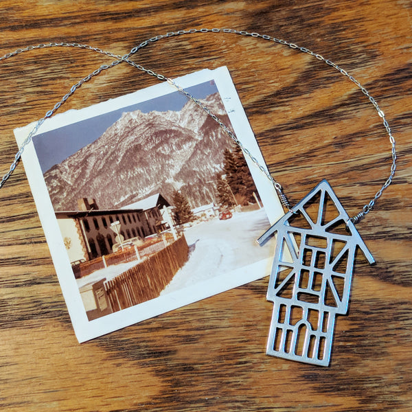 Tudor Ski Chalet Necklace with a vintage photo of a snow-topped mountain in a European ski village. Capture your winter vacation memories with Tinker jewelry.