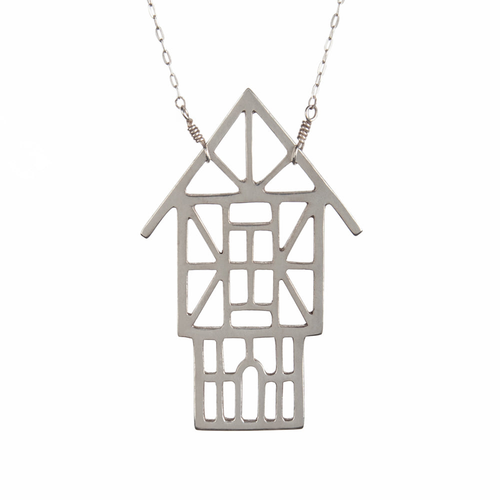The Tudor Ski Chalet Necklace is a sterling silver outline of a Tudor style house designed and made by Tinker to capture your favorite winter vacation memories.