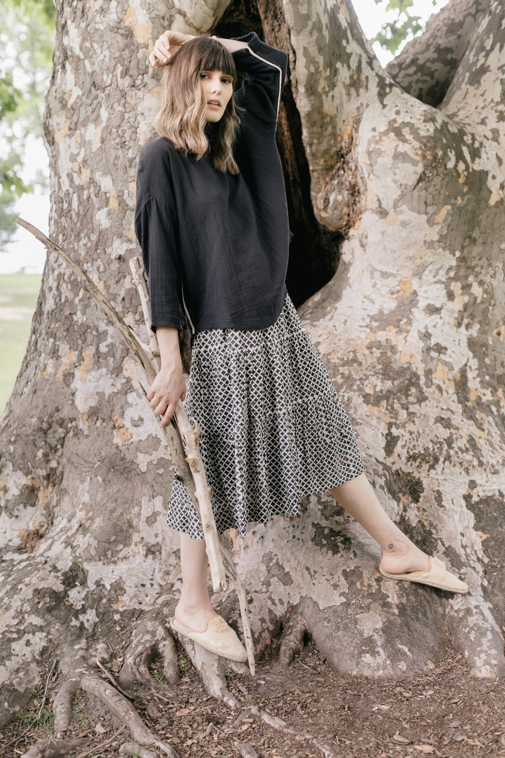 A model wearing a three quarter length sleeve double cotton cloth top in black with a silk block printed skirt.