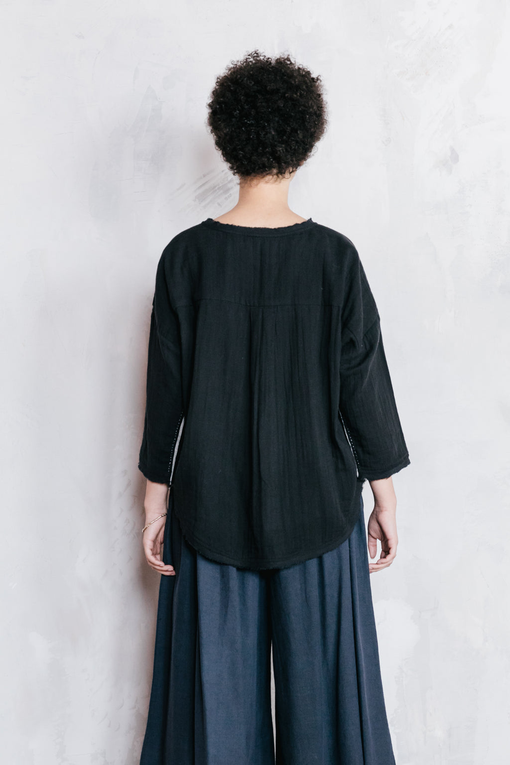 A model wearing a three quarter length sleeve double cotton cloth top in black with wide legged blue palazzo pants.
