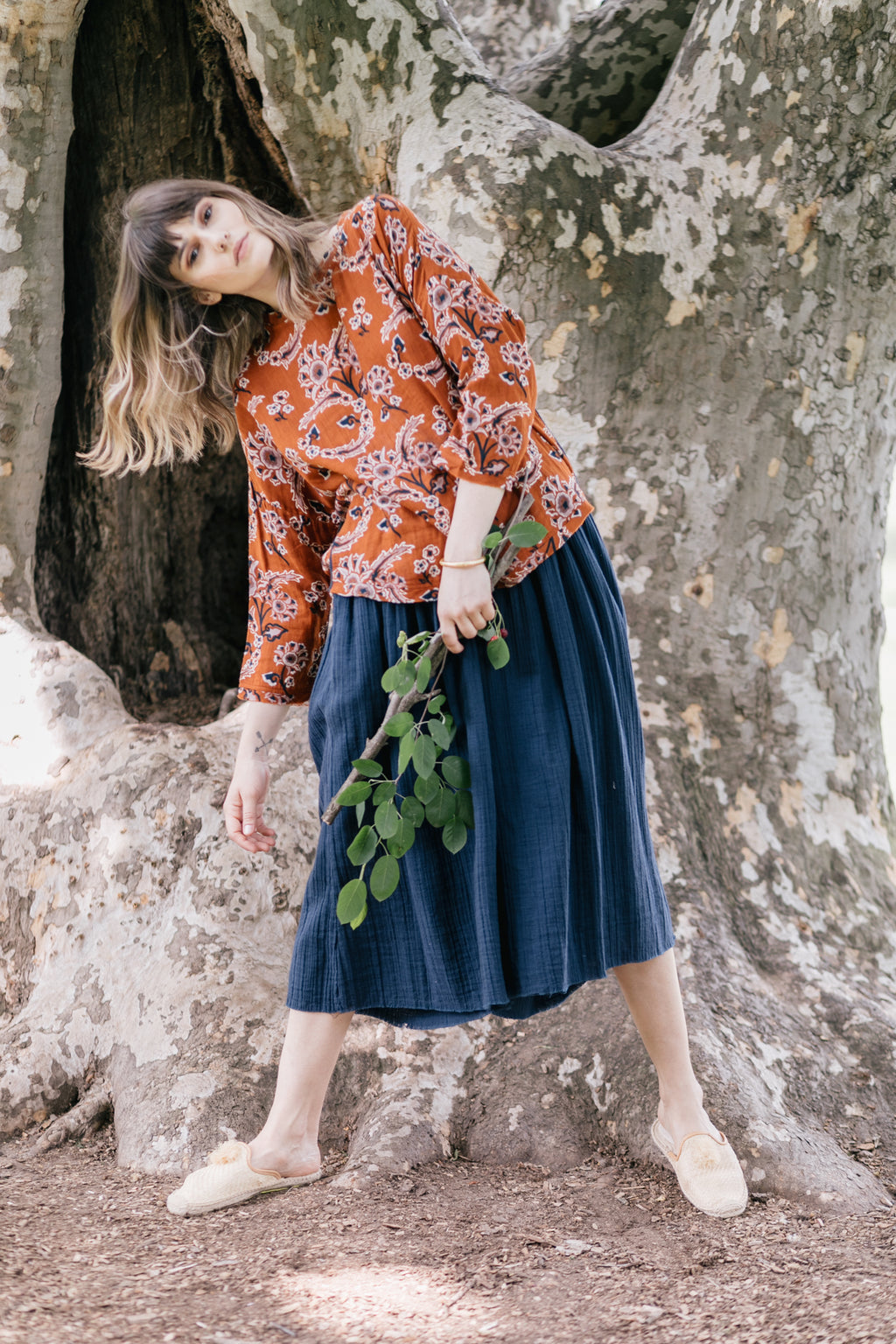 Model wearing an umber orange floral print top with a high low hem and cotton rolled sleeves paired with wide legged blue palazzo pants.