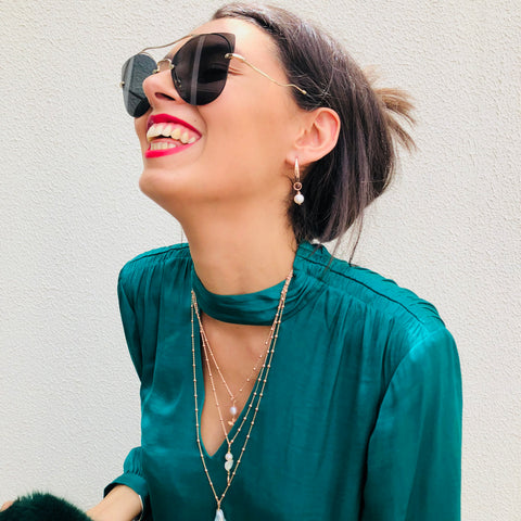 Model wearing Leoni & Vonk rose gold and white pearl drop earring and green Portmans shirt and Miu Miu sunglasses