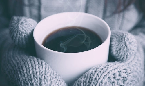 Cup of coffee held by mittens