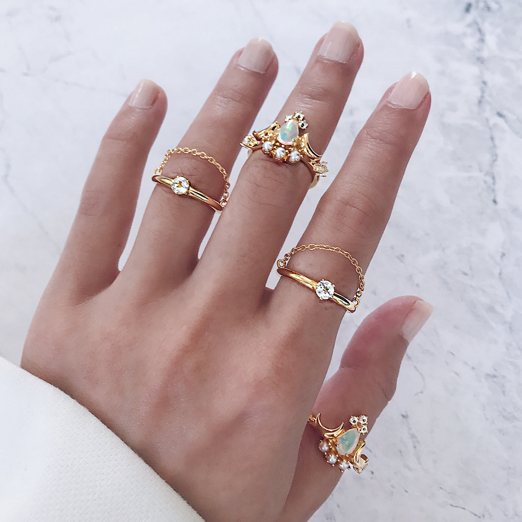 opal rings worn in a bohemian ring stack - beautiful gold white opal rings hand-set with diamonds and pearls in a pear cut jewel, mix with solitaire diamond chain rings, looks so lovely